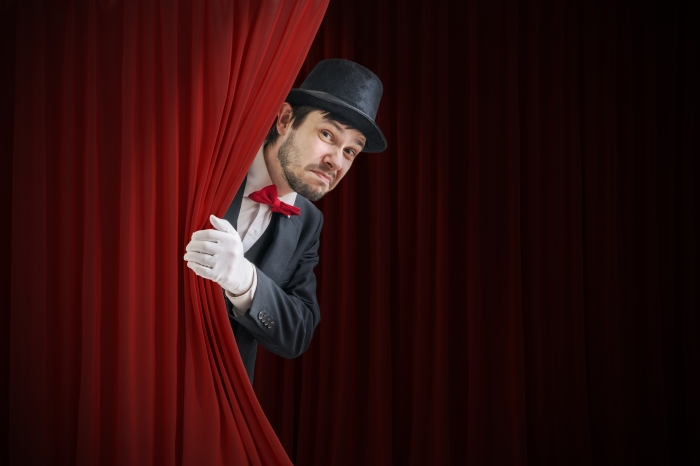 Nervous Actor Or Illusionist Is Hiding Behind Red Curtain In The
